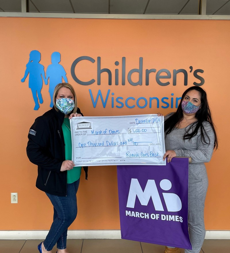 Karen Lowerr of Remedy Consulting presenting check to March of Dimes Wisconsin representative Alma Velez in New Berlin, Wisconsin.
